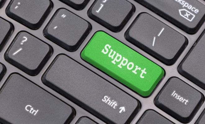 """Computer keyboard closeup with """"Support"""" text on green enter key"""